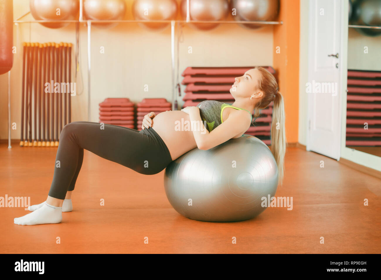 Yoga for pregnant women. Young beautiful pregnant girl in sportswear doing yoga on fitball - Stock Image