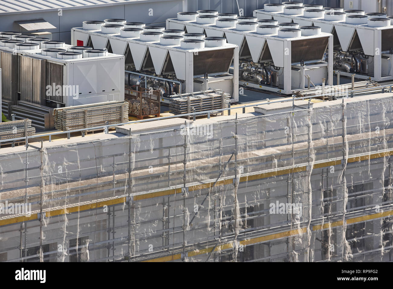Air conditioner compressors on a building rooftop under construction. Industrial Stock Photo