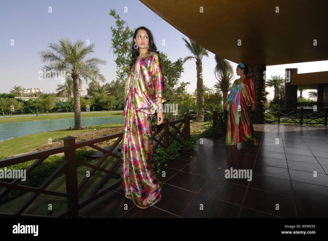 Girls of Asian nationality dressed in bright summer dresses are walking in the summer garden of a country house. - Stock Image