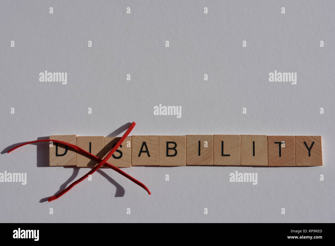 Creative Concept : Disability in wooden letters, with Dis crossed out, leaving the word Ability - Stock Image