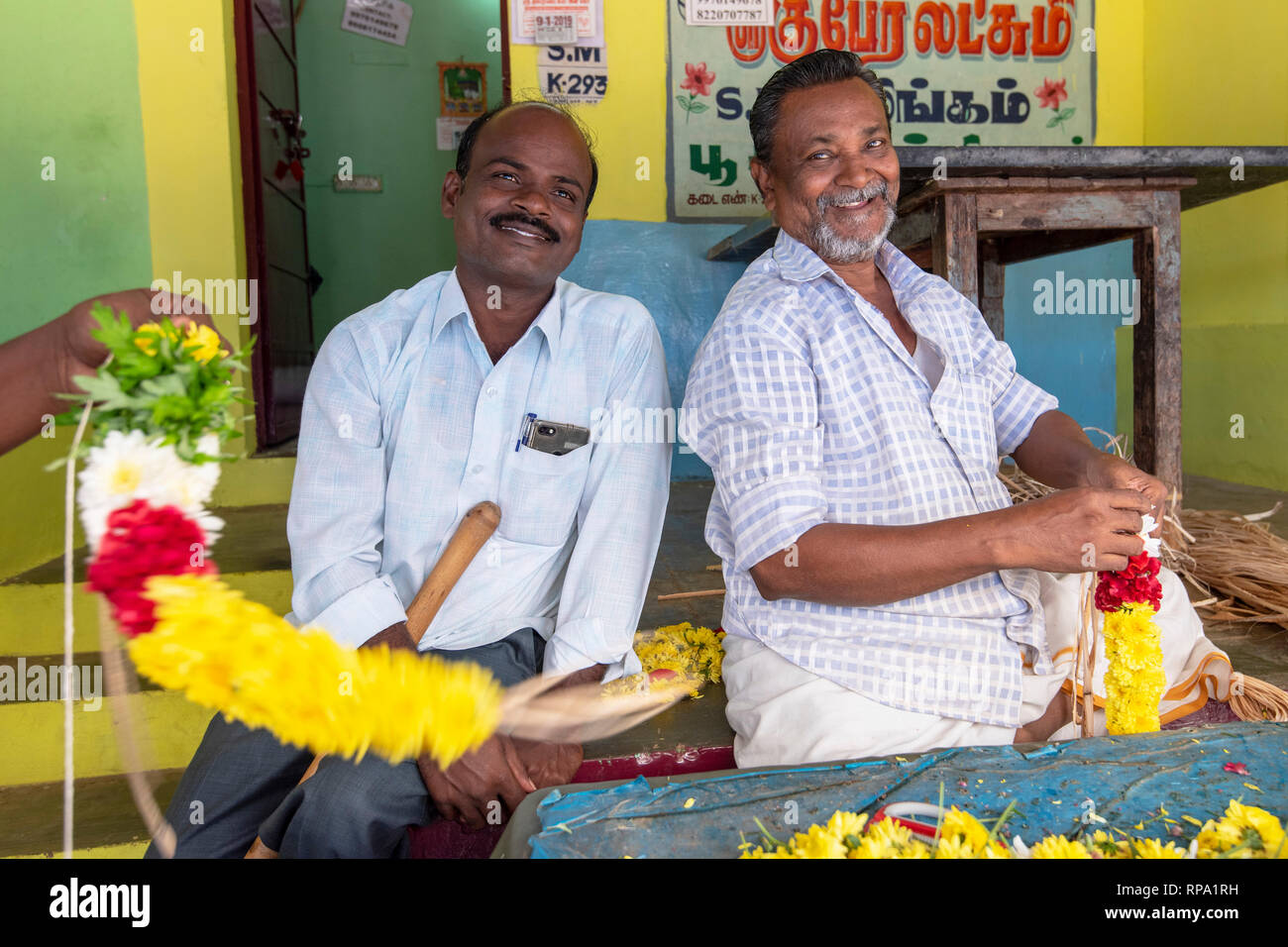 Friendly stall holders pose for the camera at the Madurai flower market while making garlands of flowers to sell. - Stock Image
