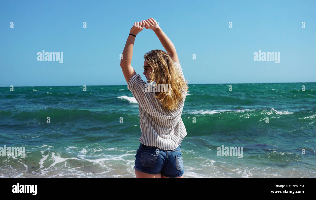 Beautiful bohemian styled and tanned girl at the beach against the backdrop of sea waves - Stock Image