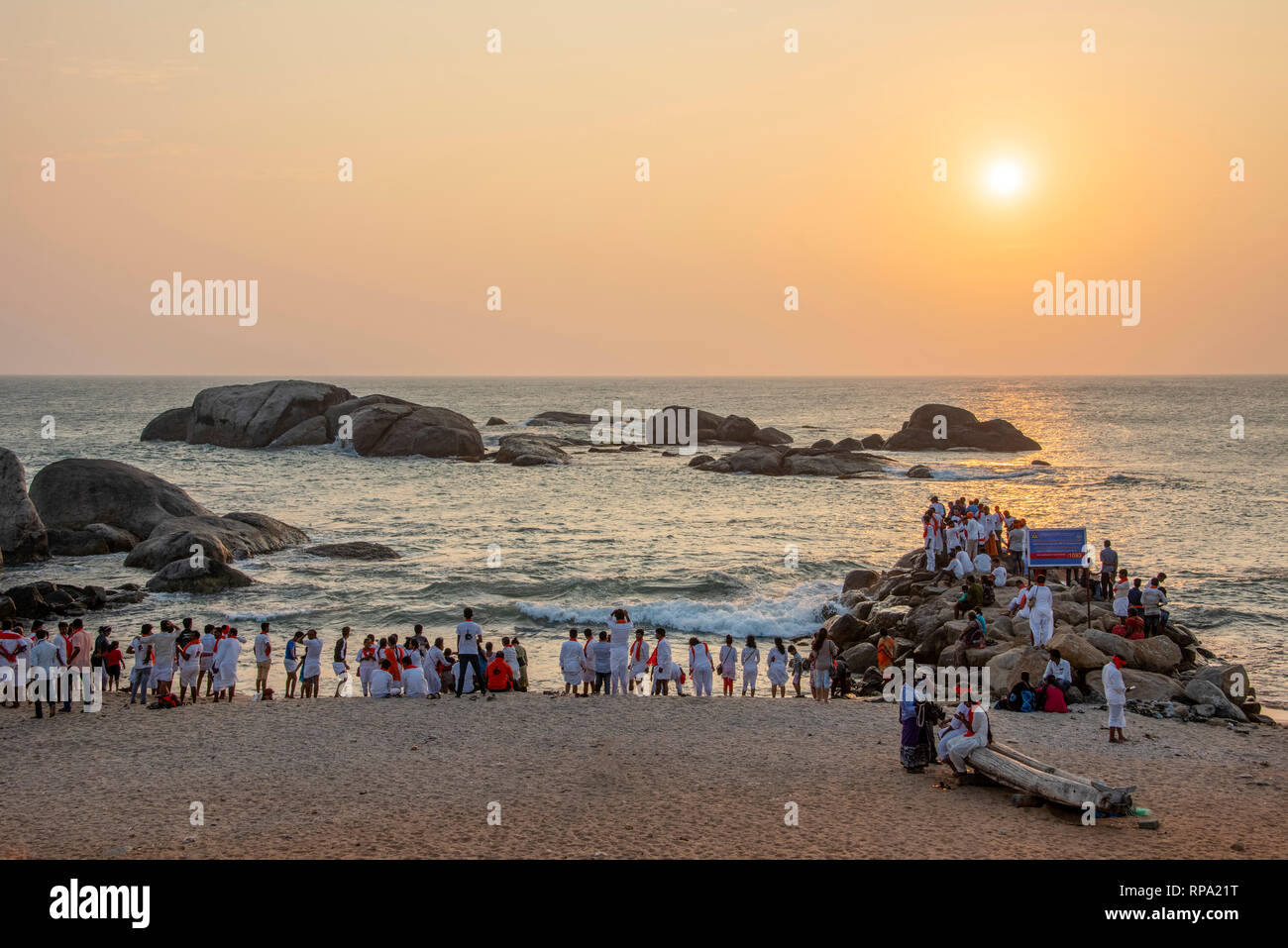 HDR image of crowds of local Indian people like to go to the beach at sunset to watch the sun go down on the beach at Sunset View Point in Kanyakumari. - Stock Image