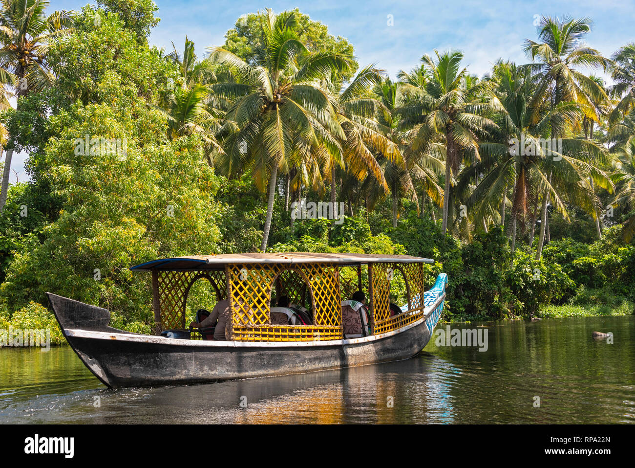 A typical day boat cruising floating on the Keralan backwaters on a sunny day with blue sky and palm trees. - Stock Image