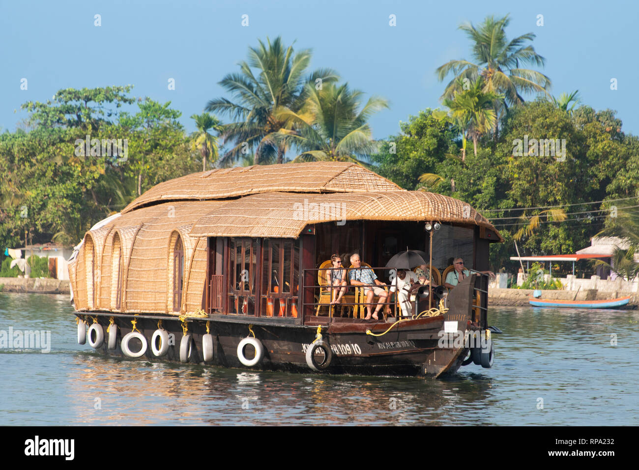 A typical example of a traditional liveaboard boat cruising floating on the Keralan backwaters on a sunny day with blue sky and palm trees. - Stock Image
