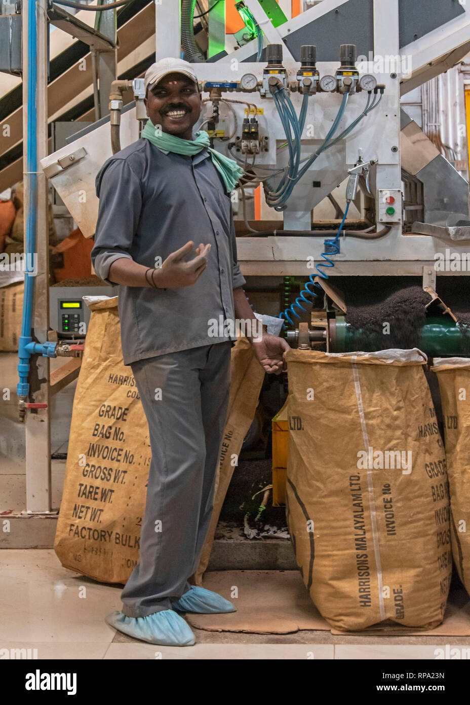 A worker at work in the Lockhart tea factory using new macinery smiling posing for the camera. - Stock Image