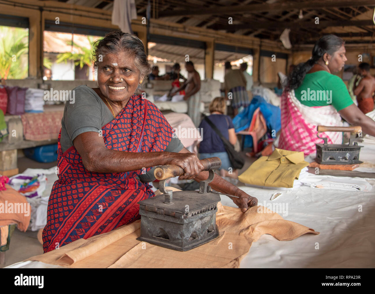 A smiling happy Indian woman ironing at Dhobi khana public laundry in fort Kochi using a traditional old iron box. - Stock Image