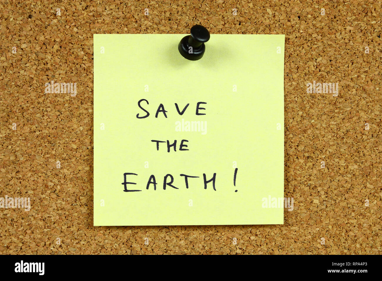 Yellow sticky note pinned to an office notice board. Save the earth - environmental message, ecology concept. - Stock Image