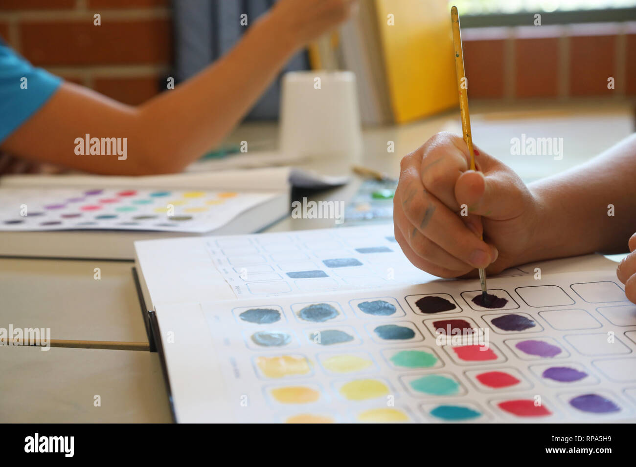 Students working in visual art process diaries exploring experimenting with colour theory. Painting in workbooks. Creative arts education concept - Stock Image