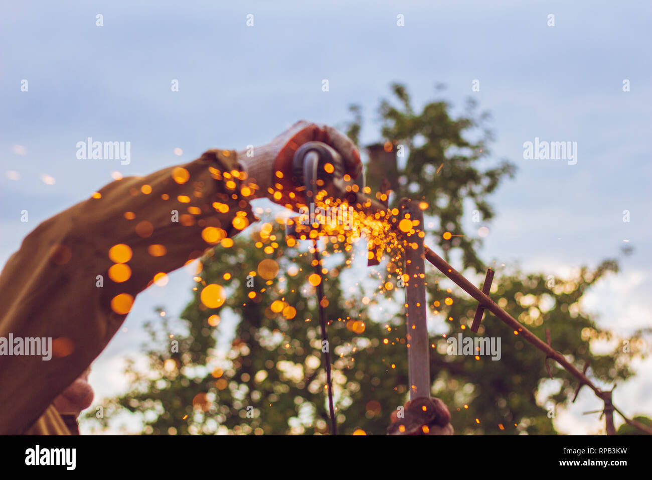 Beautiful background with sparks flying from the grinder in the process of cutting metal - Stock Image