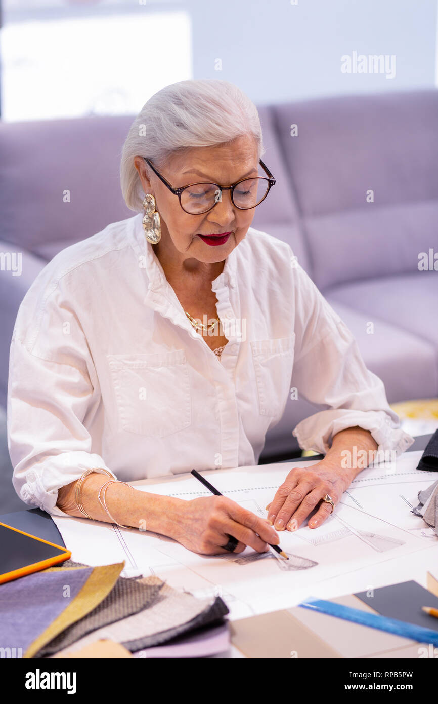 02a91e187918ae Blue-rinsed comely fancy manager in glasses successfully engaging in  designing - Stock Image
