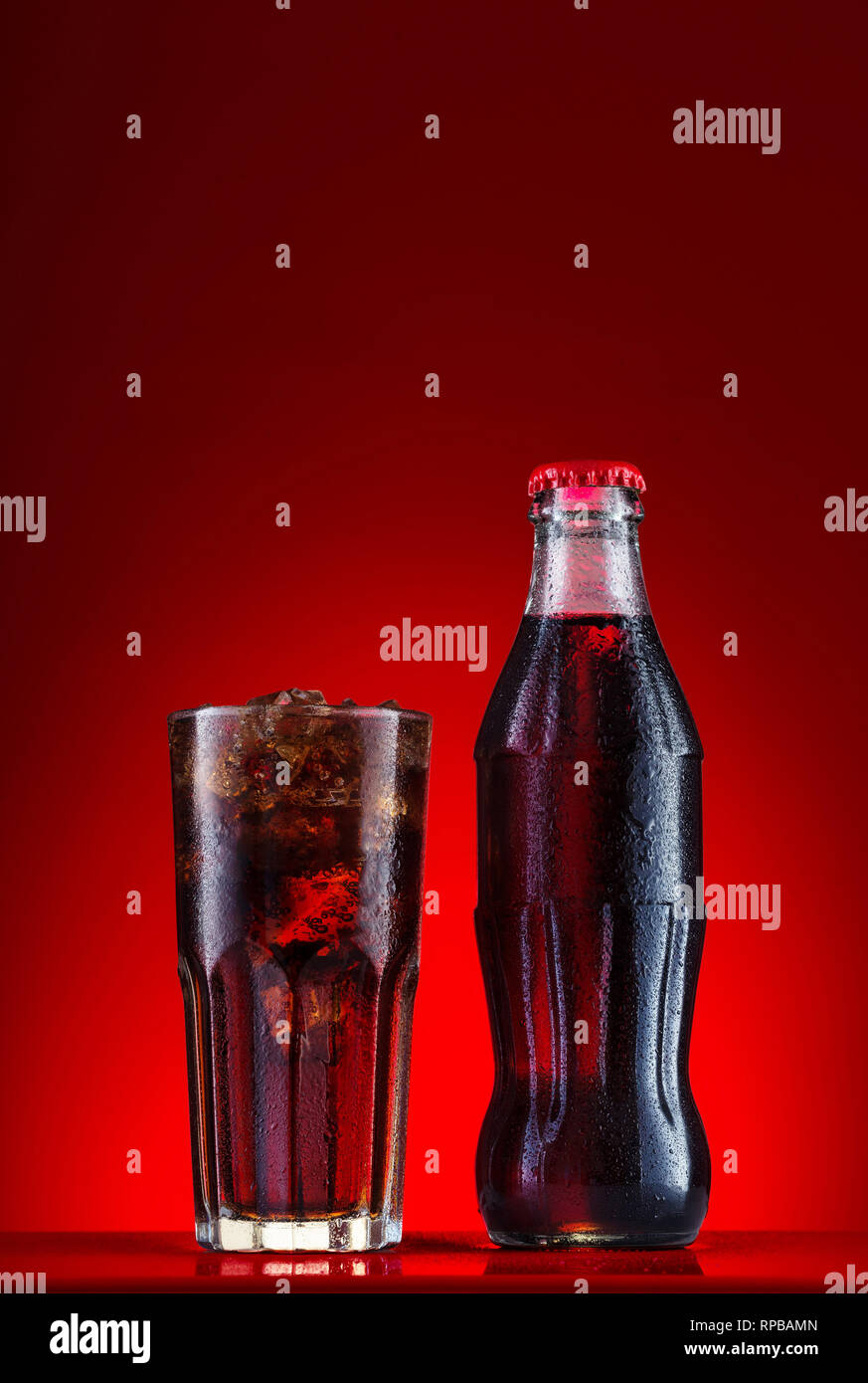 Brown carbonated drink in bottle and glass with ice - Stock Image