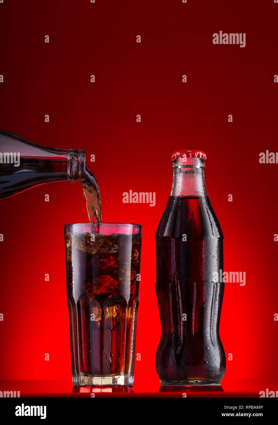 Brown carbonated drink is poured in glass with ice and bottle - Stock Image