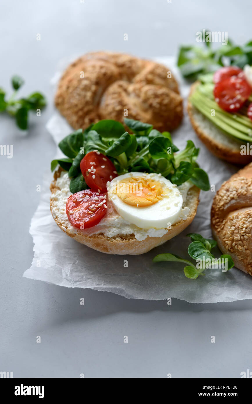 Bagel sandwiches with cream cheese, avocado, tomatoes, egg and greens on gray wooden background. Selective focus. Healthy eating or vegetarian food co Stock Photo