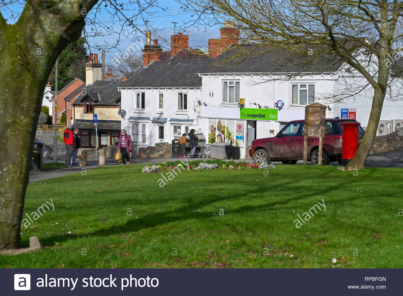 Local people visit the  Co-op store in the village of Pontesbury, Shropshire UK during an unseasonably warm February morning. - Stock Image