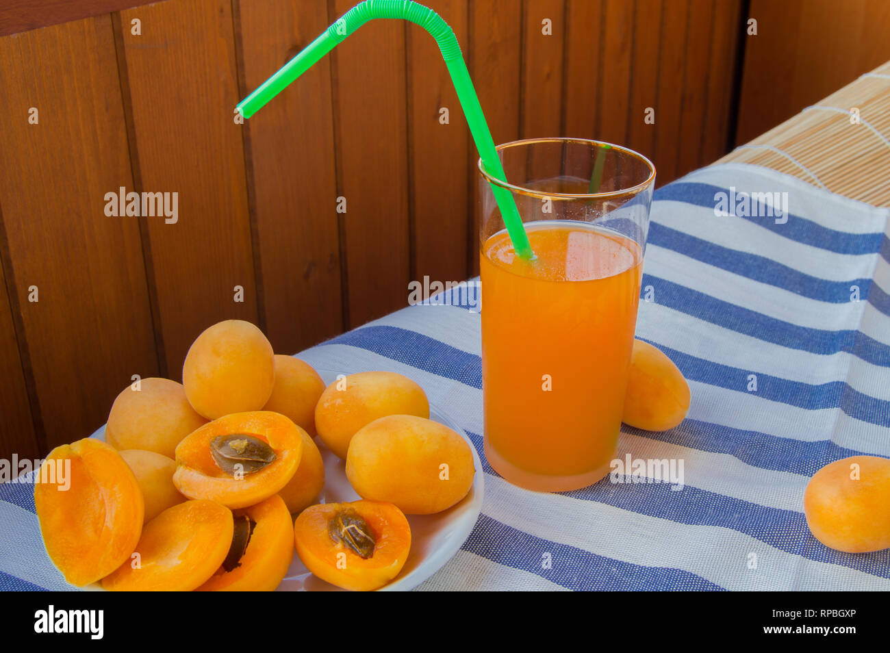 apricot juice in a Glass with straw and fruit on napkin. - Stock Image