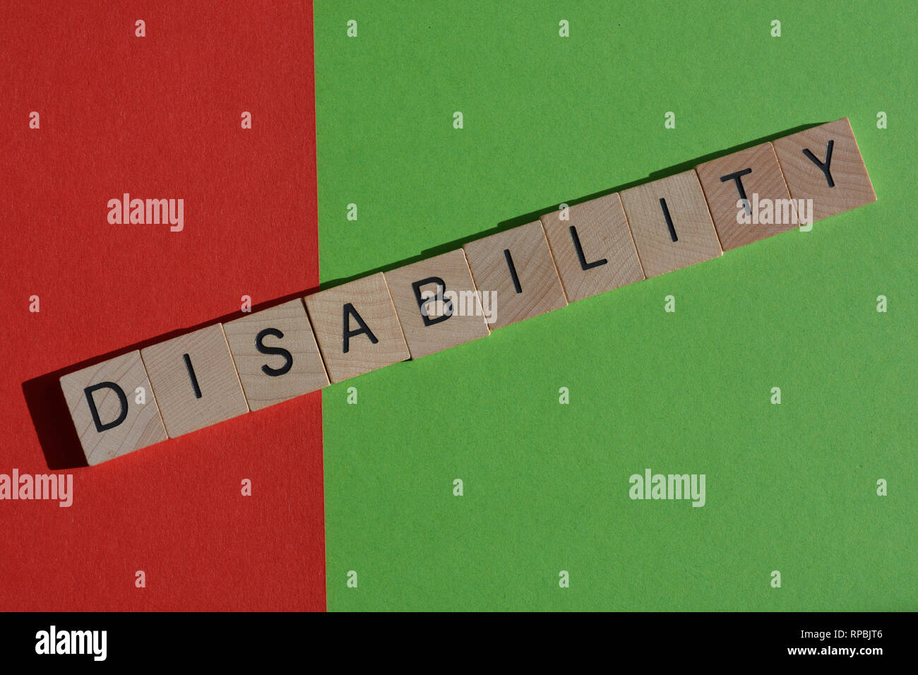 Creative Concept : Disability in wooden letters,  Dis on red and Ability on green background, - Stock Image