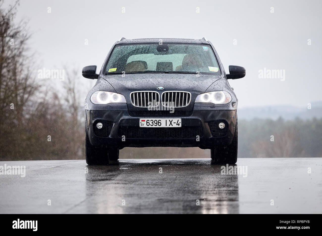 GRODNO, BELARUS - OCTOBER 2016: BMW X5 front view with glowing headlights standing on wet asphalt under rain covered with raindrops over gray rainy sk - Stock Image