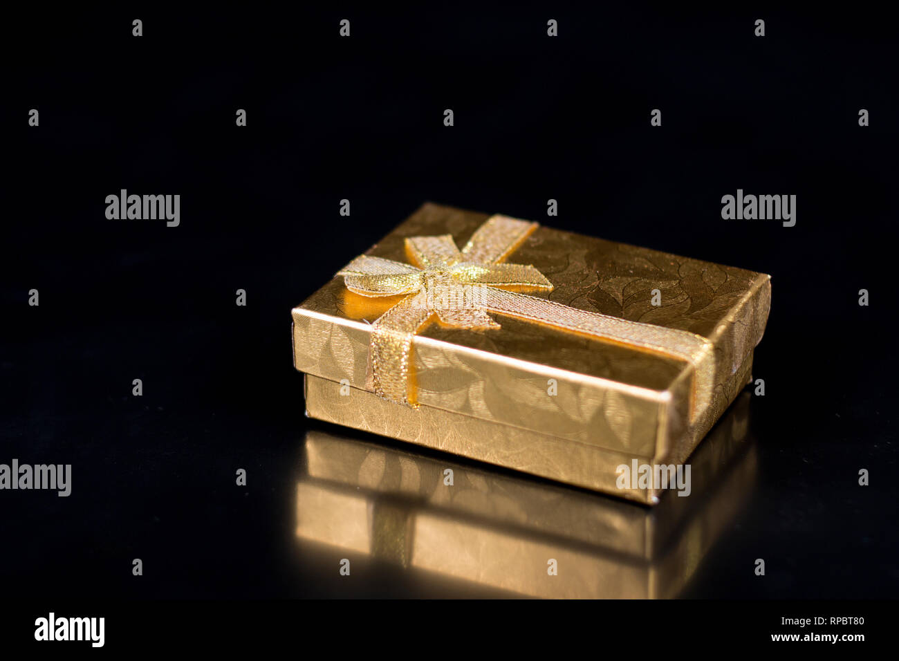Golden jewellery box on a black glossy background - Stock Image
