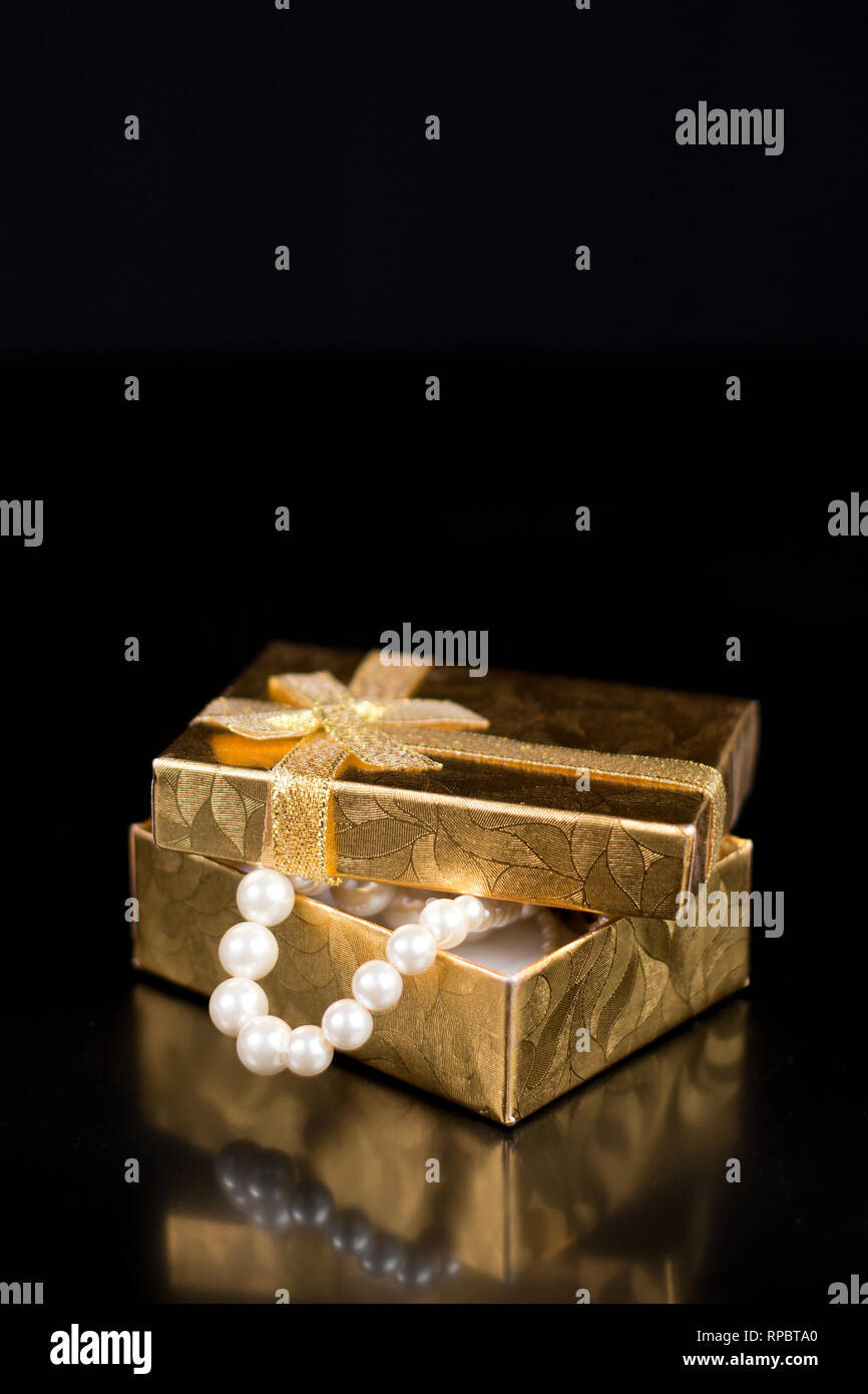 Golden jewellery box with shiny pearls on a black glossy background - Stock Image