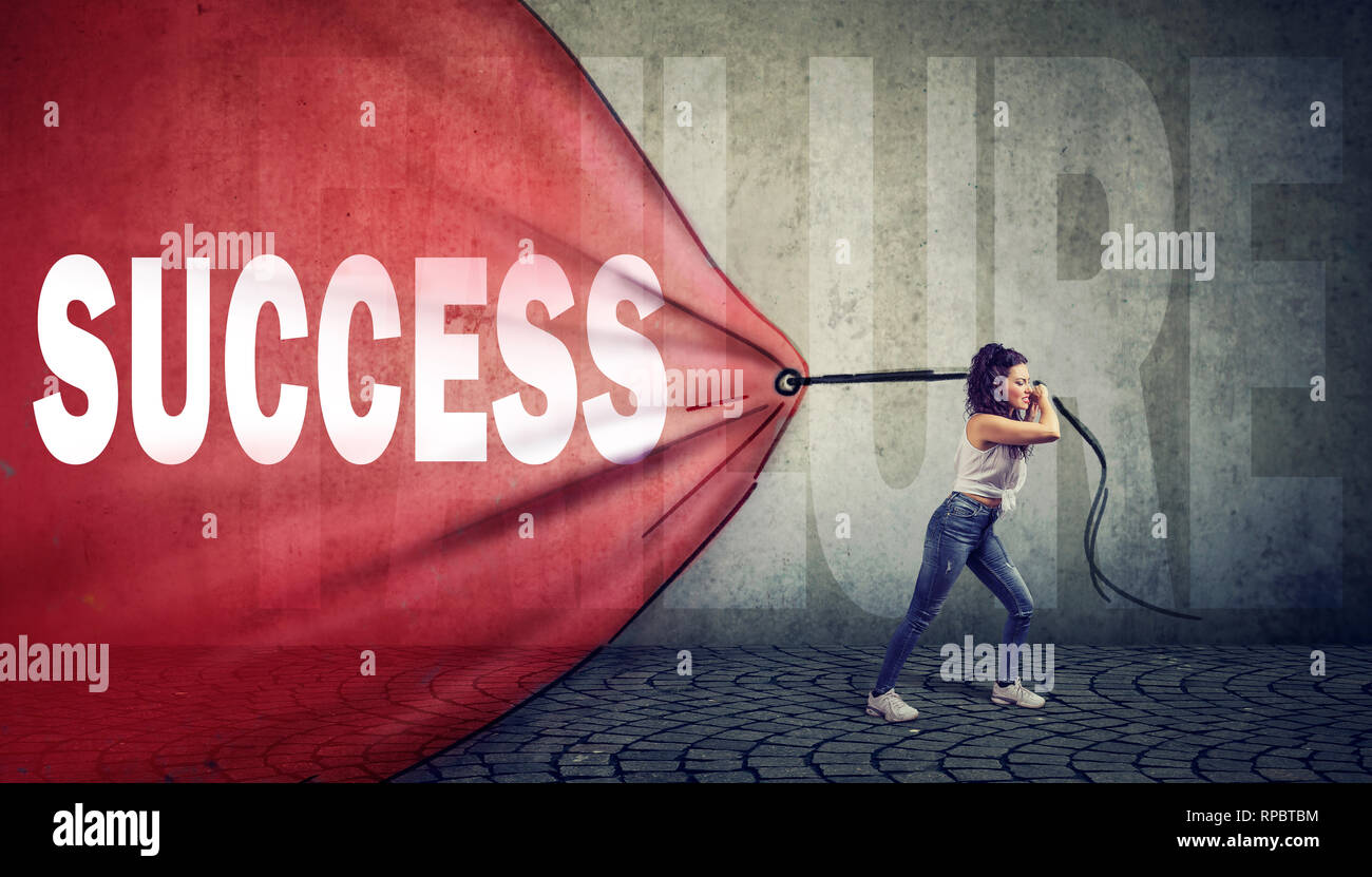 Motivated young woman pulling a red banner with success word overcoming a failure - Stock Image