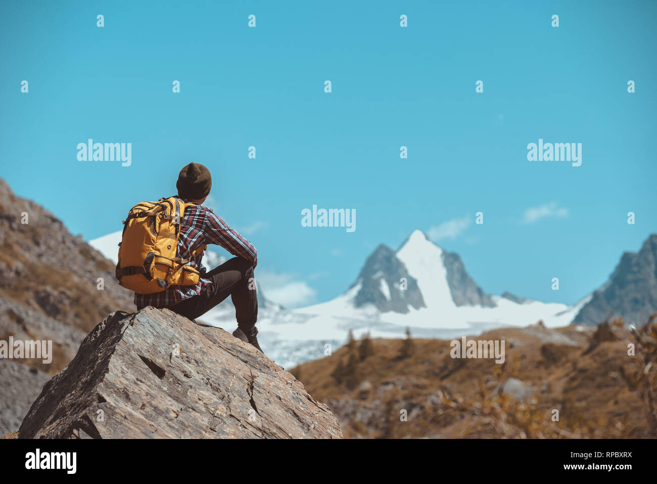Man hiker with backpack sits on big rock and looks at white mountain with glacier Stock Photo
