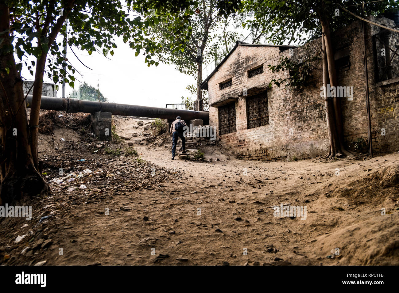 A man about to cross the railway tracks that lies beyond this building close to Pragati Maidan. - Stock Image