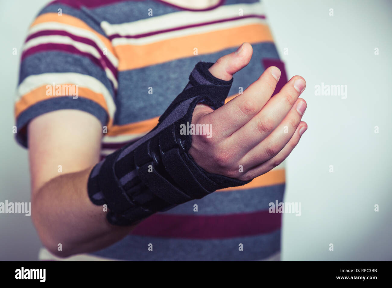 Man with hand in orthopedic black orthosis - Stock Image