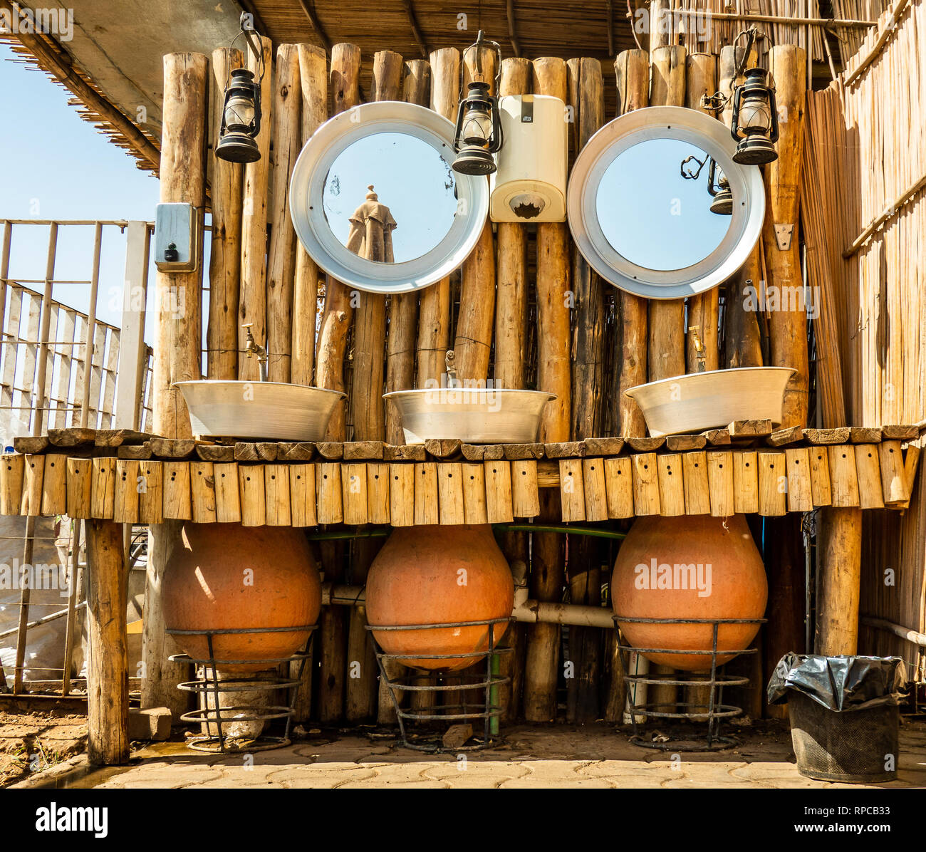 Khartoum, Sudan, February 5. 2019: Open washroom of a good restaurant on the Nile with water amphorae, metal bowls, faucets and petroleum lamps behind - Stock Image