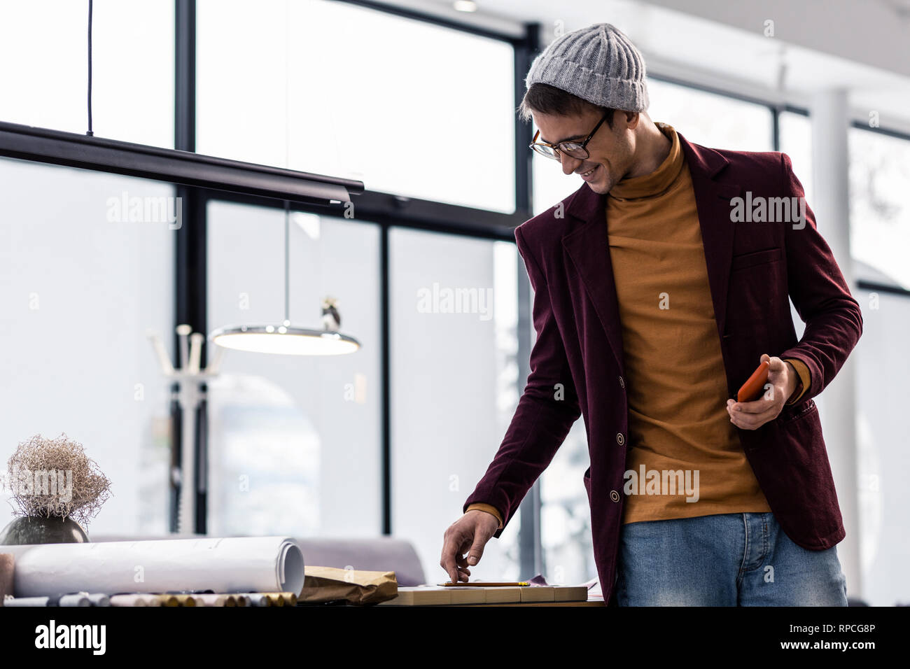 17ee2de171f4e9 Energetic pleasant fashionably worn manager looking at office desk - Stock  Image