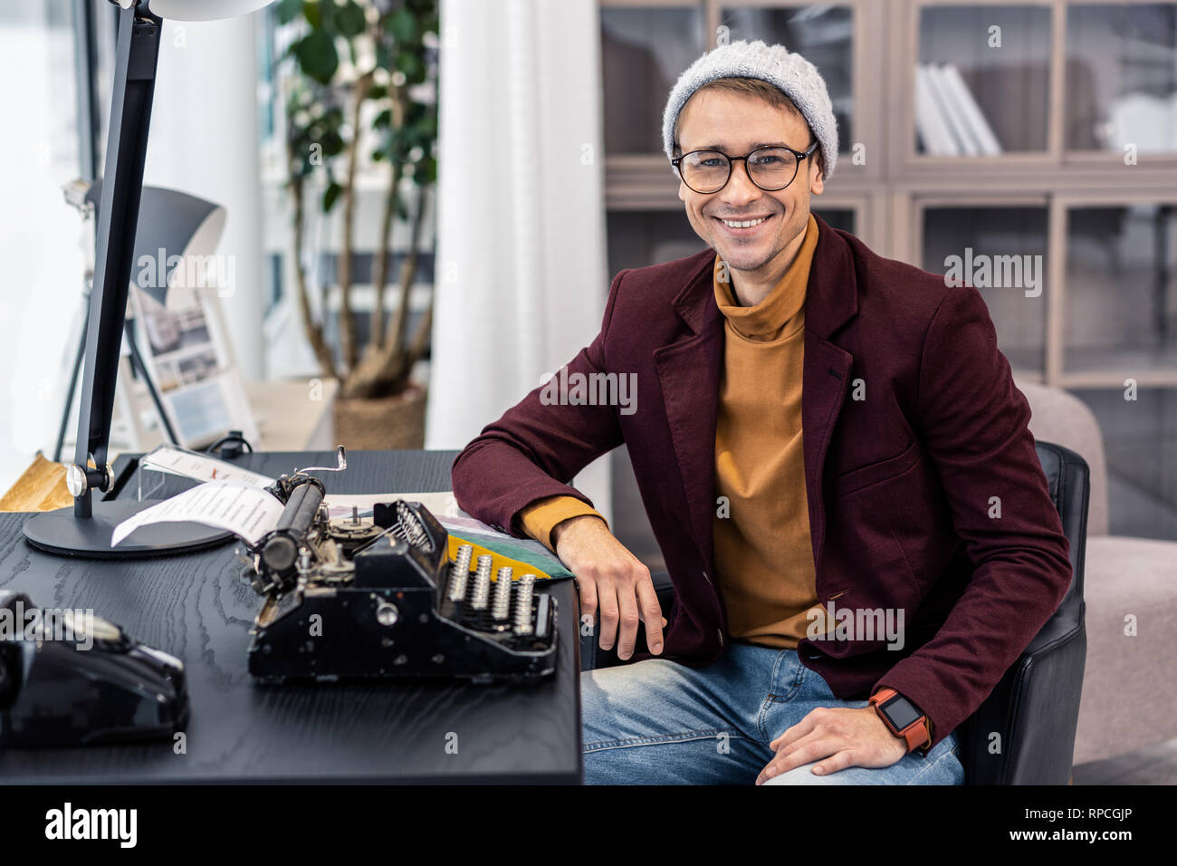 Fanciable young dark-haired man posing at desk with typewriters - Stock Image