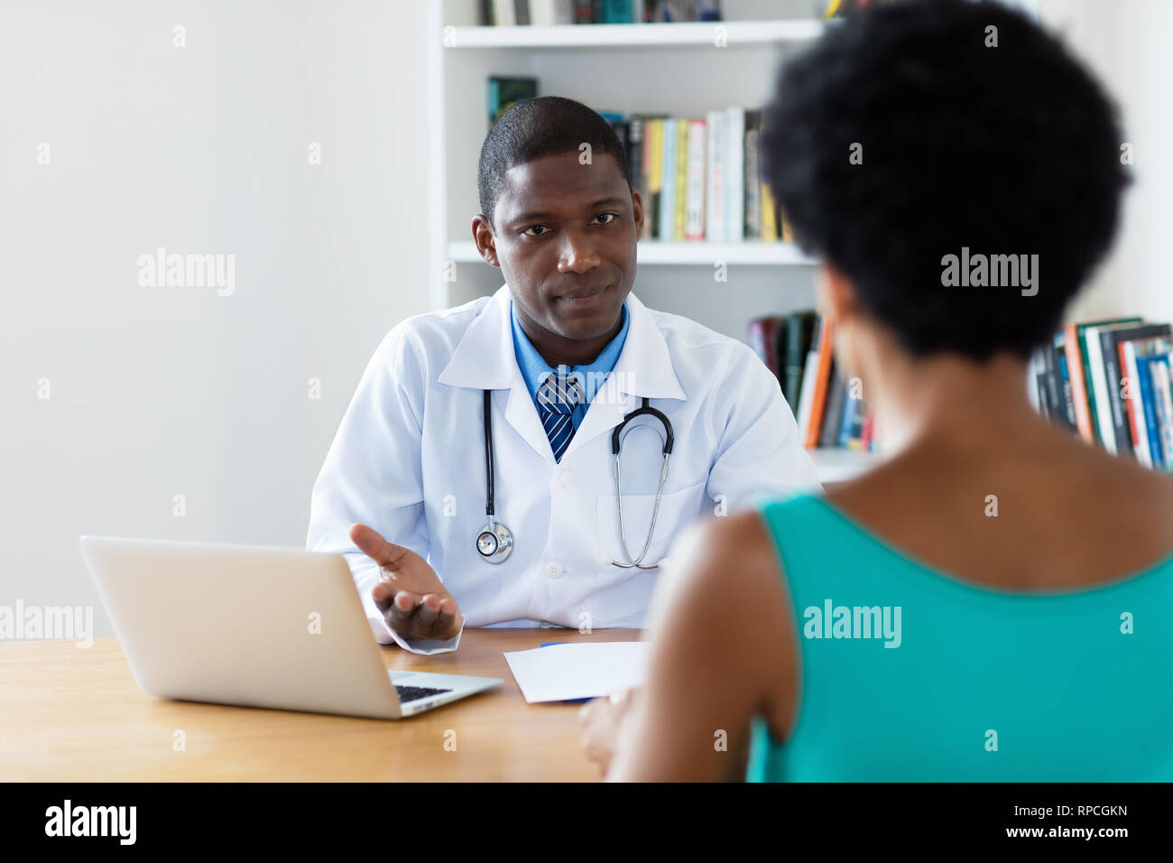 African american doctor explaining diagnosis to female patient at hospital - Stock Image