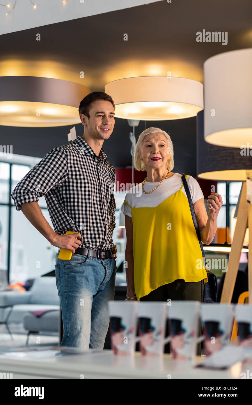 Charming aging woman being in lighting store with tricenarian boyfriend - Stock Image