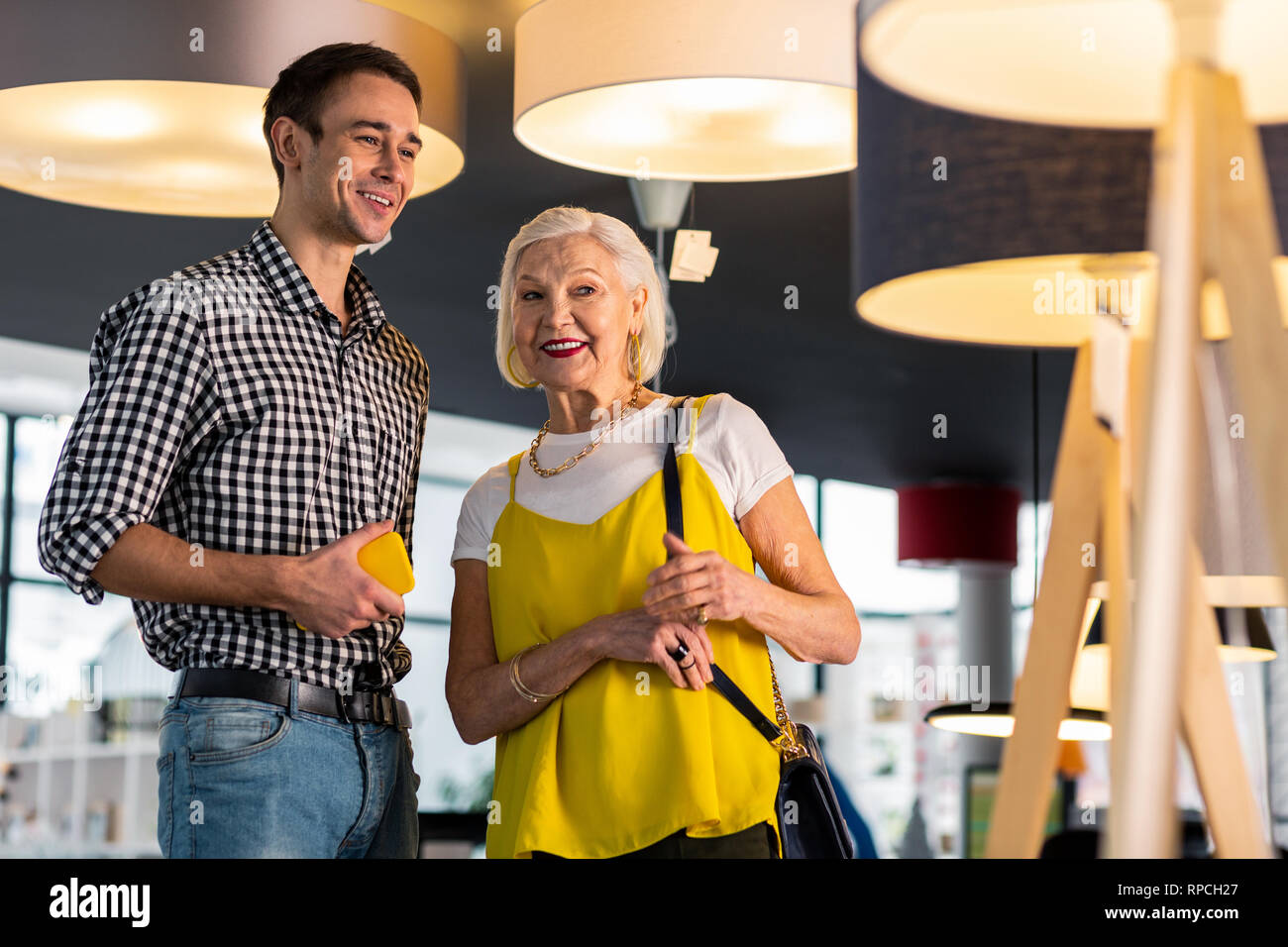 Beaming gorgeous senior lady discussing lamps buying with younger beau - Stock Image