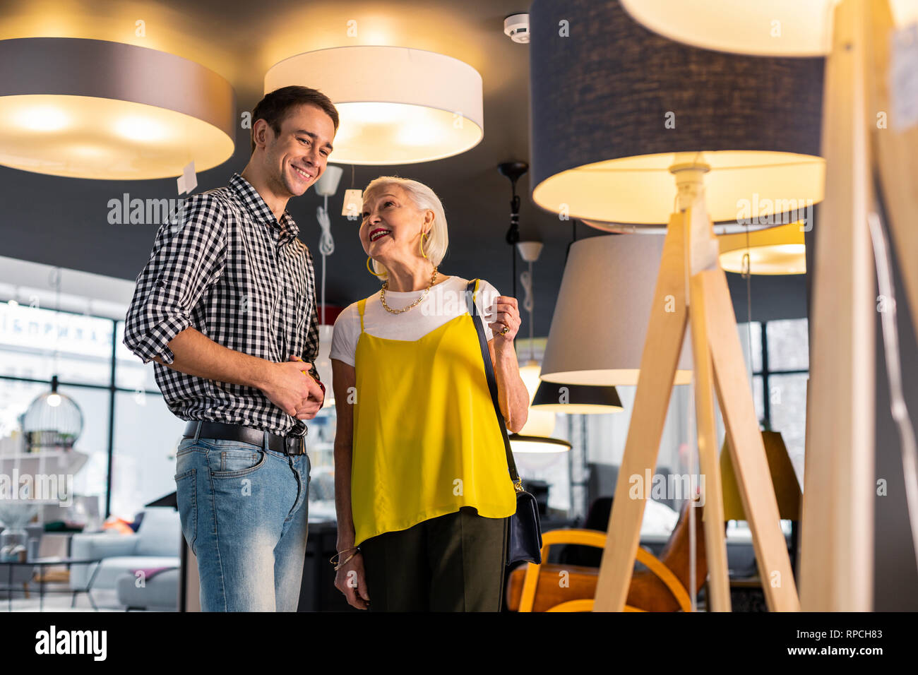 Happy stylish aging mother looking affectionately at adult handsome son Stock Photo