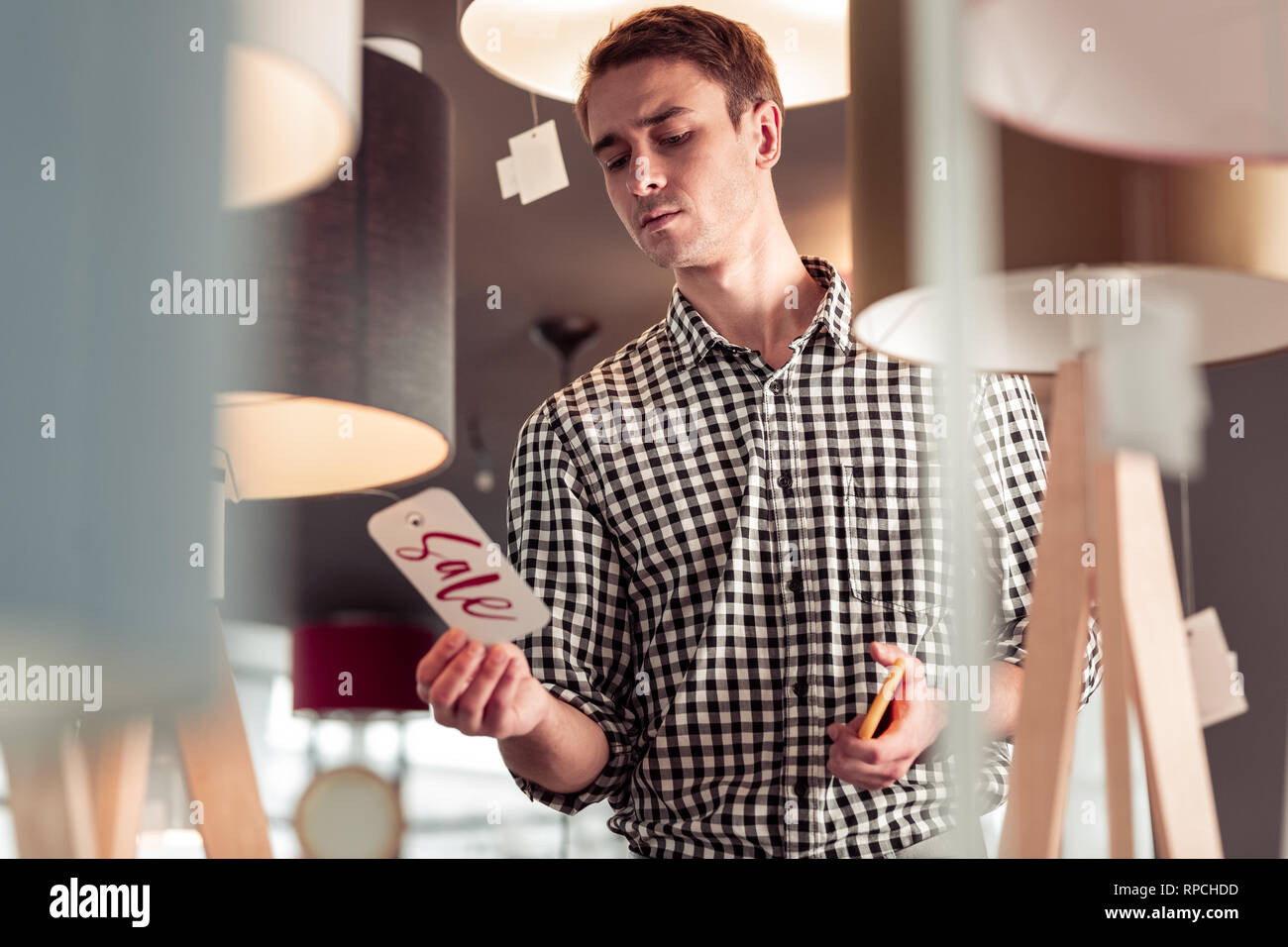 Attractive stylish male surprisingly looking at sale sign tag - Stock Image