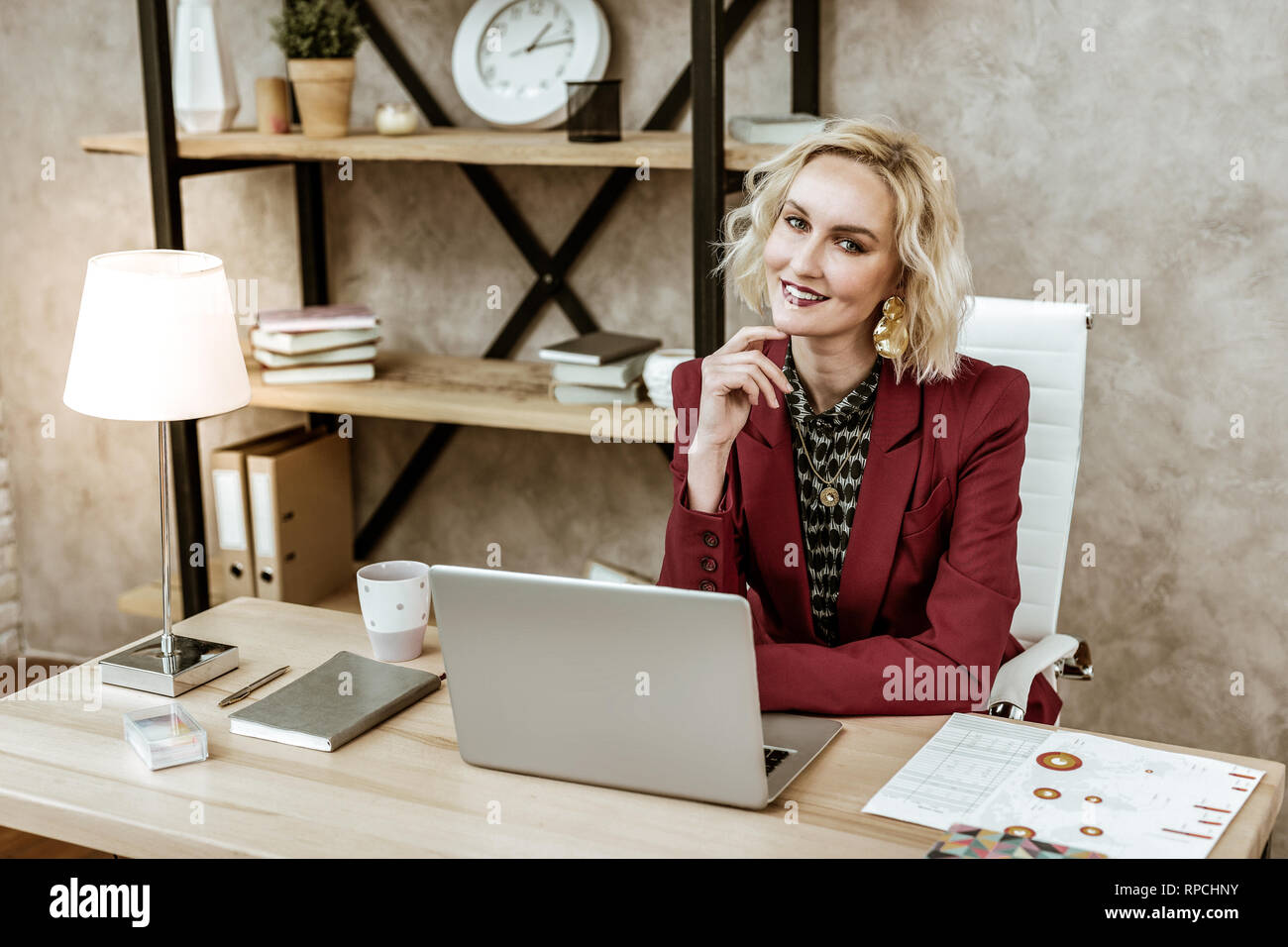 Coquettish blonde woman sitting at the desk in front of laptop - Stock Image