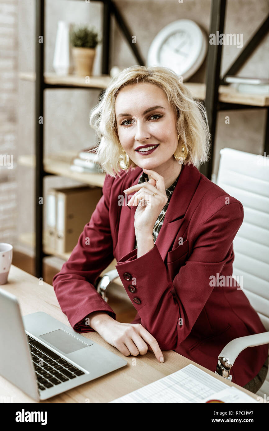 Coquettish short-haired woman with intense makeup working in office - Stock Image
