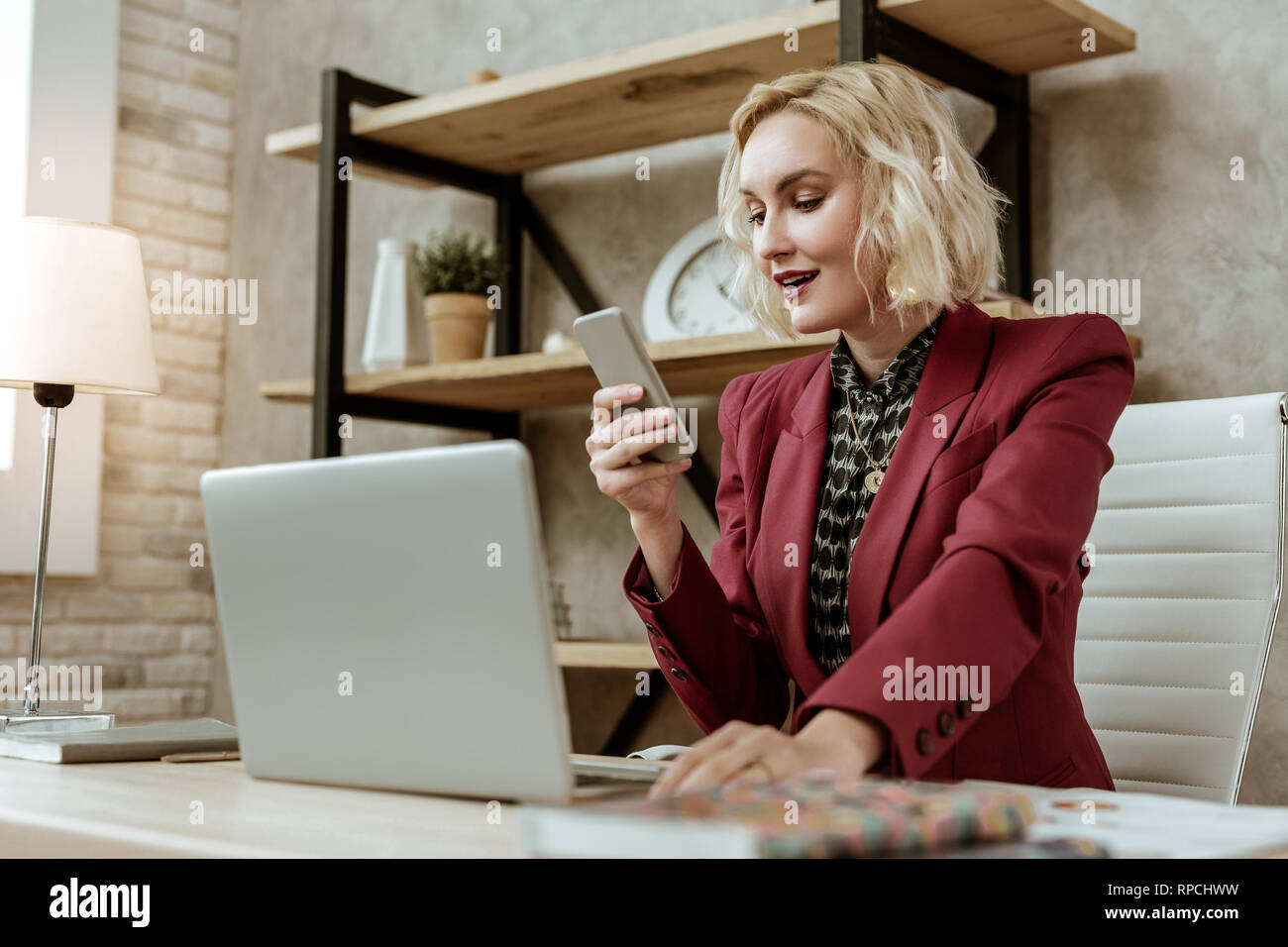 Surprised smiling blonde lady being happy with received message Stock Photo