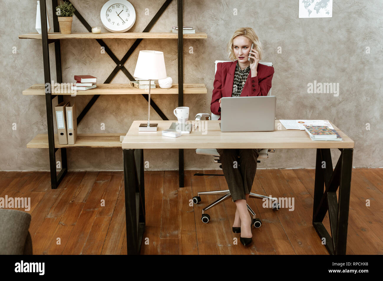 Serious attentive business woman having call related to her work - Stock Image
