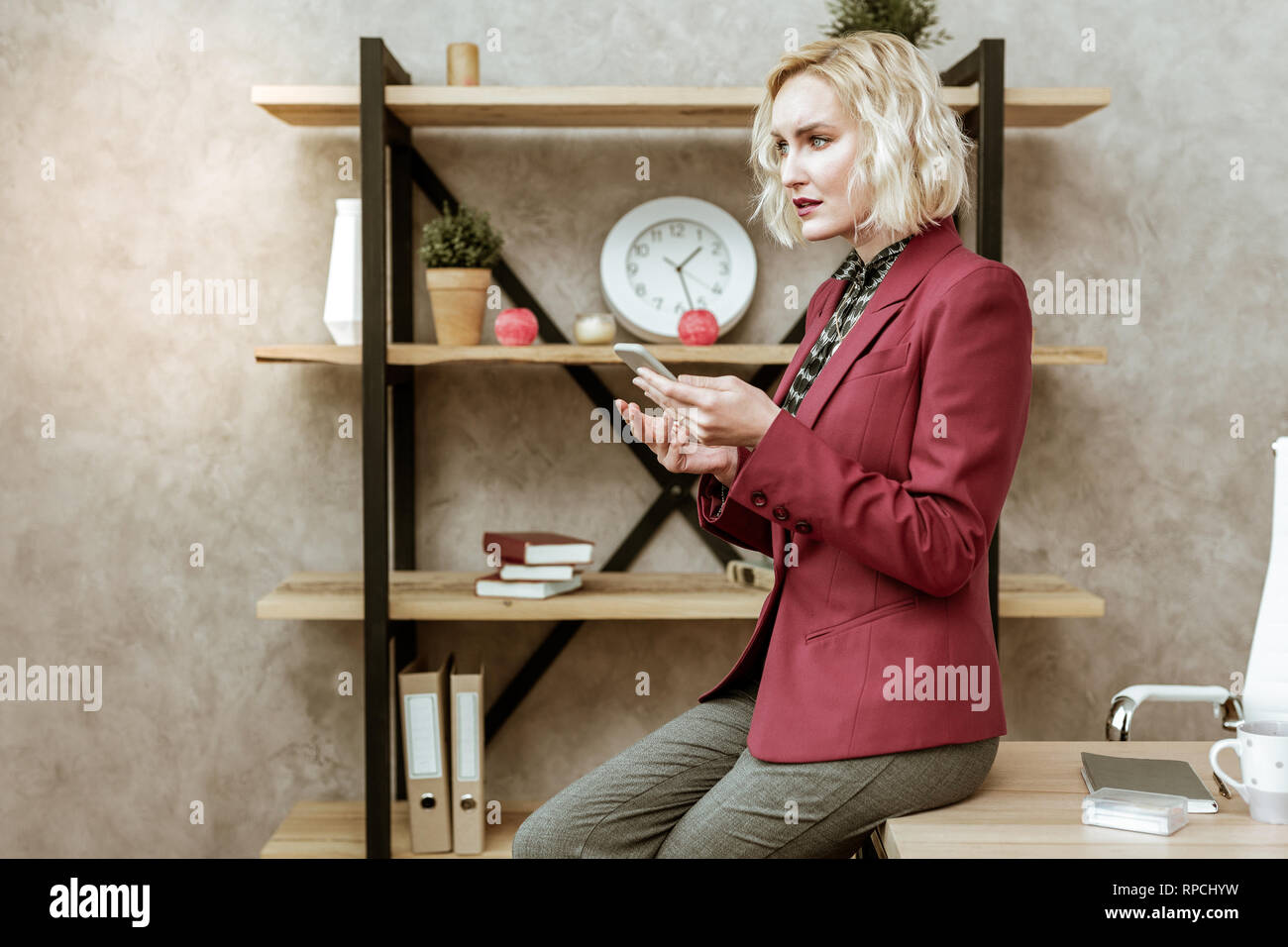 Serious good-looking lady in red outdated jacket leaning on table surface - Stock Image