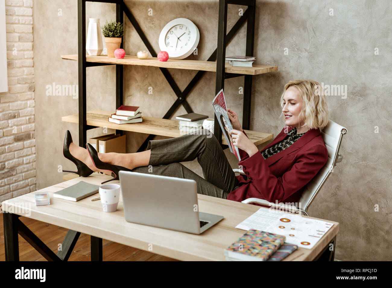 Unprofessional short-haired woman putting her legs on office table - Stock Image