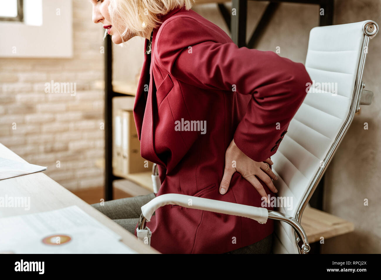 Blonde adult businesswoman having pain in back because of passive lifestyle - Stock Image