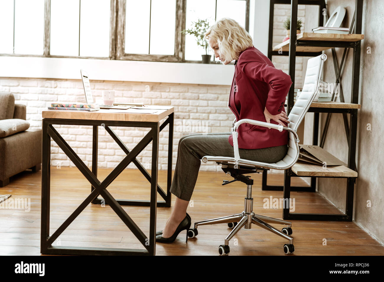 Unhappy beautiful lady in office outfit and high heels - Stock Image