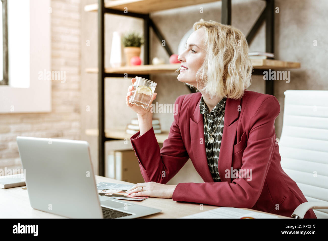 Curious appealing lady with wide smile quenching thirst with water - Stock Image
