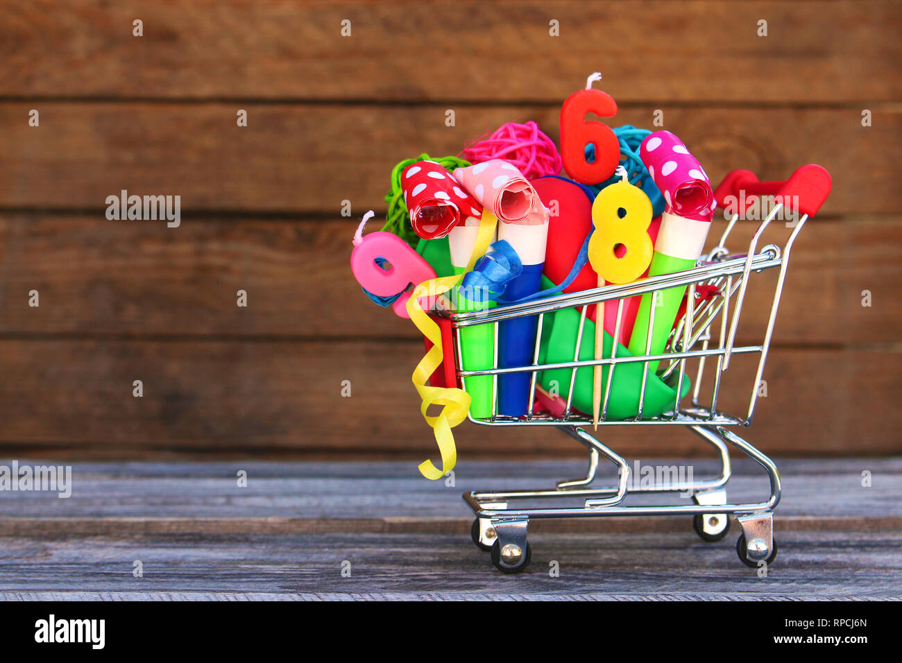 Shopping cart with items for birthday celebration on wooden background. Stock Photo