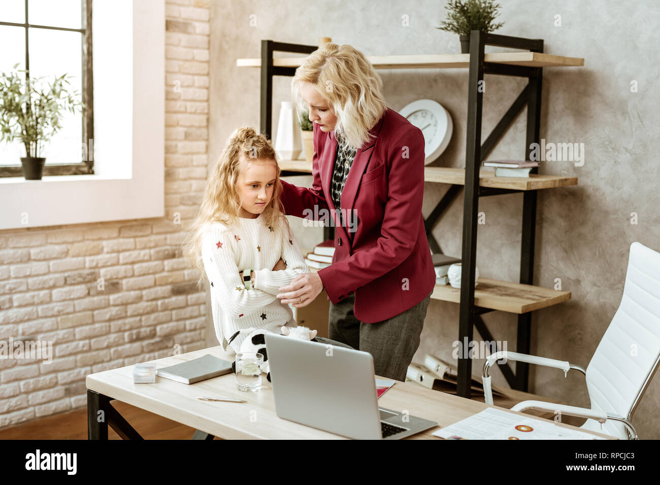 Caring short-haired mother settling down her daughter feelings - Stock Image