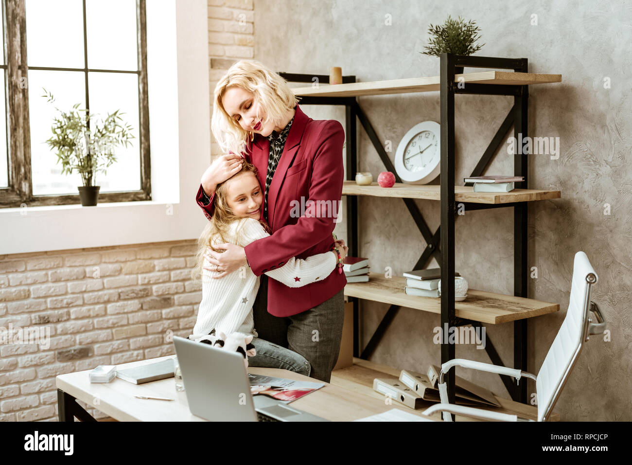 Peaceful short-haired smiling mother expressing all her love - Stock Image