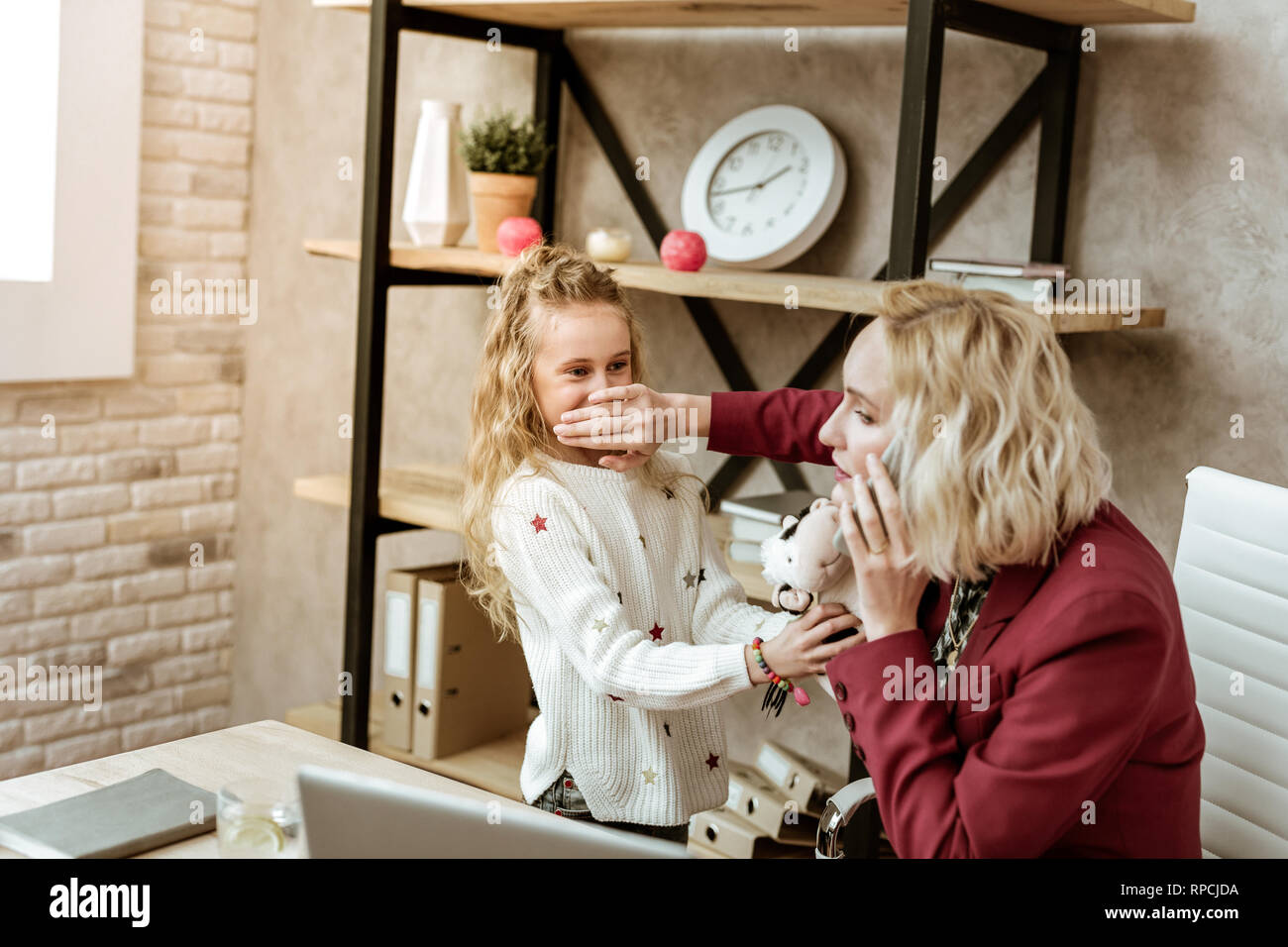 Irritated blonde businesswoman shutting mouth of her daughter - Stock Image