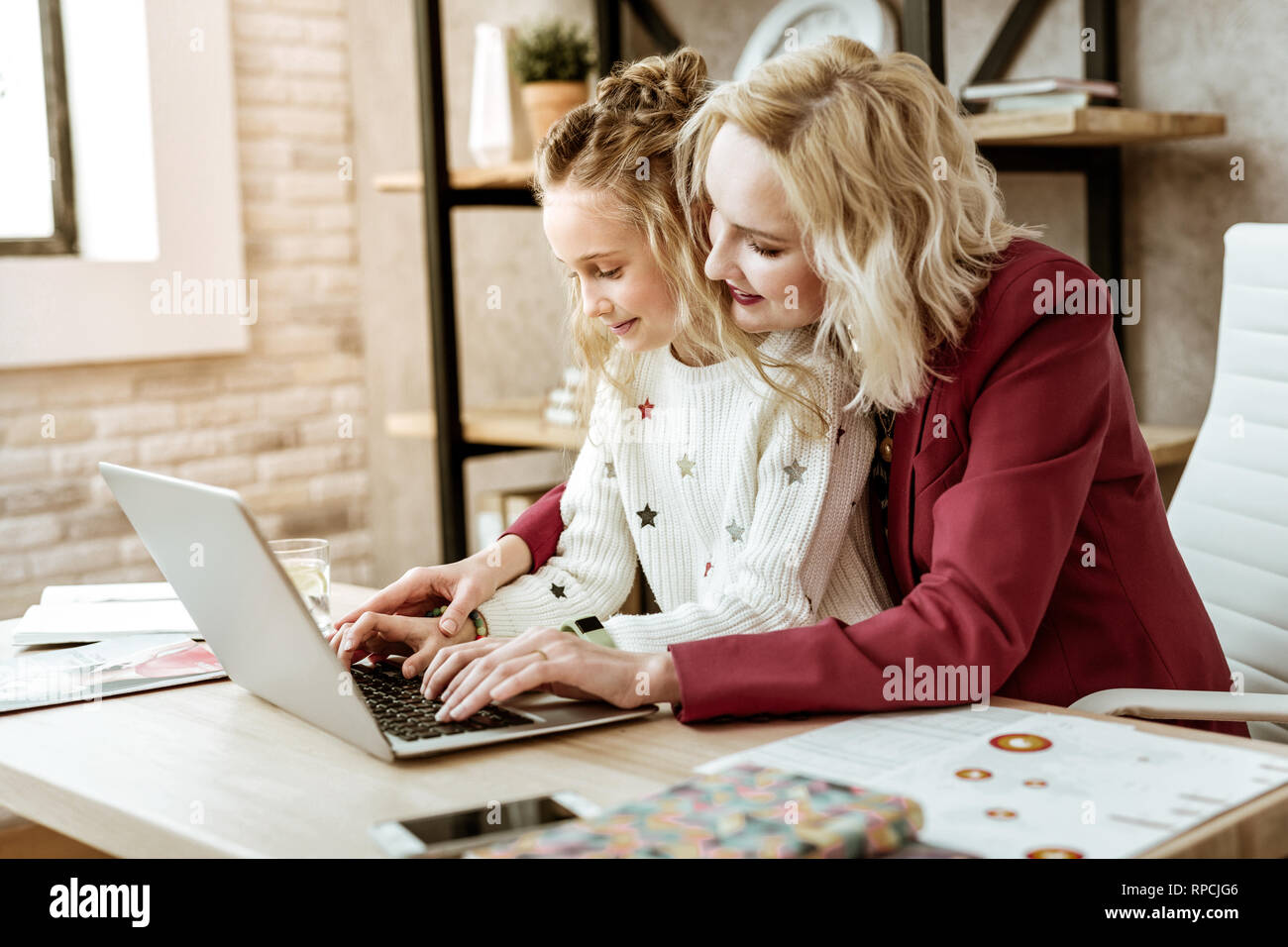 Gentle short-haired mother showing right way of typing - Stock Image